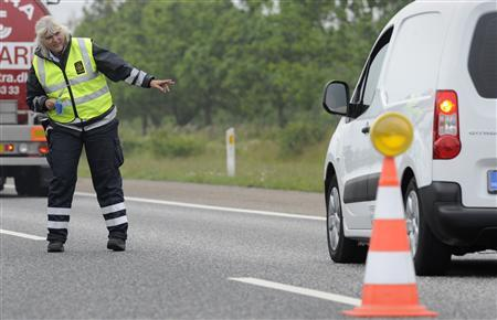 A Danish customs officer signals to a driver at the German-Danish border crossing in Froslev on July 5, 2011. REUTERS/Fabian Bimmer