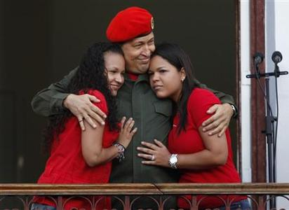 Venezuela's President Hugo Chavez hugs his daughters Rosa (L) and Maria while appearing to supporters on a balcony of Miraflores Palace soon after his return to the country from Cuba, where he underwent surgery and treatment for cancer, in Caracas July 4, 2011. REUTERS/Carlos Garcia Rawlins