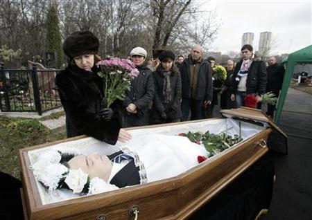 Widow Natalia Zharikova (L) grieves over her husband Sergei Magnitsky's body during his funeral at a cemetery in Moscow November 20, 2009. Magnitsky, a suspect in a tax evasion case against Hermitage, once Russia's biggest investment fund, died of heart failure in prison on Monday, state prosecutors said. REUTERS/Mikhail Voskresensky