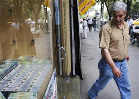 A man looks at Iranian gold coins as he leaves a currency exchange shop in Tehran's business district July 5, 2011. REUTERS/Morteza Nikoubazl