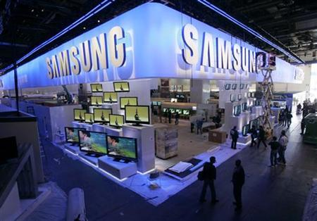 A worker cleans the sign hanging over the Samsung booth at the 2007 International Consumer Electronics Show (CES) in Las Vegas, Nevada January 7, 2007. REUTERS/Rick Wilking