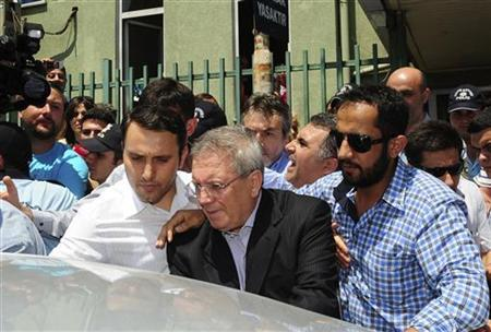 Fenerbahce Chairman Aziz Yildirim (2nd R) is escorted by plainclothes police officers as he leaves from a hospital in Istanbul July 7, 2011. REUTERS/Stringer