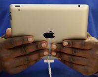 <p>Un miembro del personal sostiene el nuevo iPad2 de Apple en su tienda de Londres REUTERS/Luke MacGregor</p>