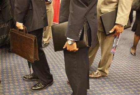 Attendees at a job fair line up for an interview carrying their resumes in leather bags in a Washington hotel, August 6, 2009. TREUTERS/Jason Reed