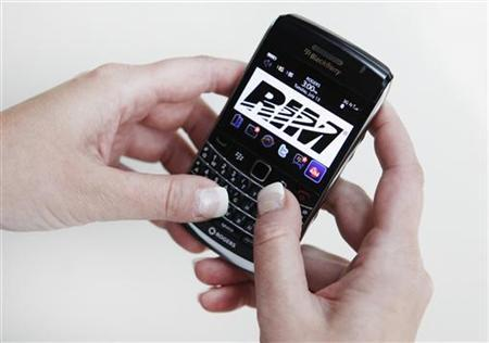 A person poses while using a Blackberry Bold 2 smartphone made by Research in Motion (RIM), July 13, 2010. REUTERS/Mark Blinch