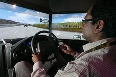 <p>Kumar Chinnaswamy texts on his mobile phone while driving in a simulator at the LG booth during the 2010 International Consumer Electronics Show (CES) in Las Vegas, Nevada, January 7, 2010. REUTERS/Steve Marcus</p>