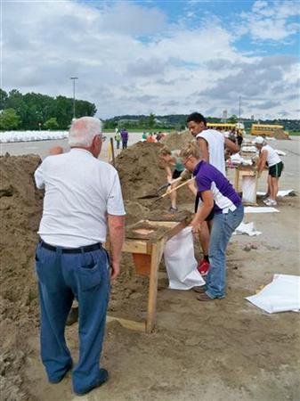 Leland Christiansen (L) of Council Bluffs, Iowa and Mindy Young, a 4-H leader from Doniphan County, Kansas, fill sandbags in Council Bluffs, Iowa July 7, 2011. REUTERS/Michael Avok