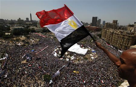 An Egyptian waves a national flag as protesters gather in Tahrir square in Cairo July 8, 2011. REUTERS/Mohamed Abd El-Ghany