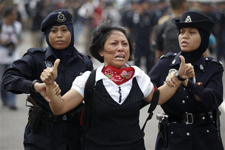 A female supporter of the ''Bersih'' (Clean) electoral reform coalition reacts as she is detained by police during clashes with police in downtown Kuala Lumpur July 9, 2011. REUTERS/Damir Sagolj