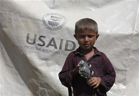 Sajad, 7, who has been displaced by flooding, holds his toy jeep outside his family tent with the weather sheet donated by USAID, while taking refuge on an embankment near Kari Mori, some 32 km (20 miles) from Dadu, in Pakistan's Sindh province October 5, 2010. REUTERS/Akhtar Soomro