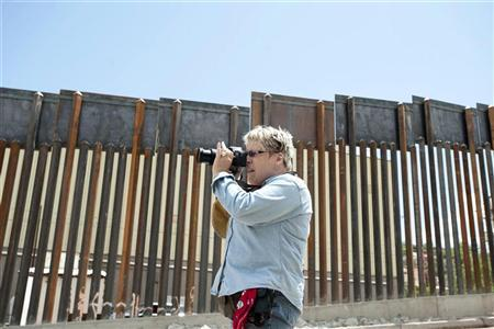 Gail Schirmer, 61, of Tucson, Arizona, takes pictures of the border wall along the Arizona- Mexico border in Nogales, Arizona. July 8, 2011. ARIZONA-BORDER/TOUR REUTERS/Laura Segall