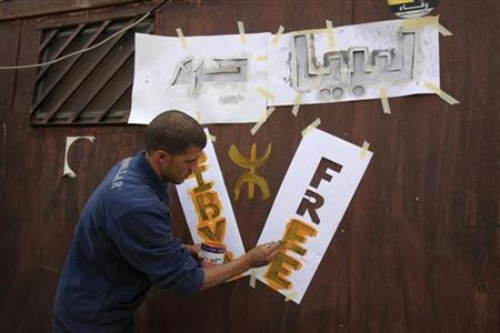 A rebel fighter paints ''Free Libya'' on a shed at a checkpoint outside the Libyan town of Kabaw in the Western Mountain region, about 230 km (140 miles) southwest of the capital Tripoli, May 11, 2011. Fighting in the Western Mountain region, home to the Berber ethnic minority, has intensified since the rebels seized the Dehiba border crossing into Tunisia last month, opening a key artery for supplies. REUTERS/Zohra Bensemra