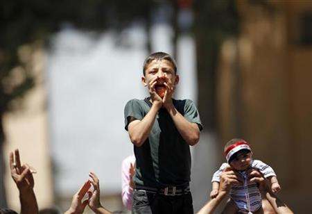 A Syrian refugee boy shouts slogans during a protest against Syrian President Bashar al-Assad at a refugee camp in the Turkish border town of Yayladagi in Hatay province July 1, 2011. REUTERS/Osman Orsal