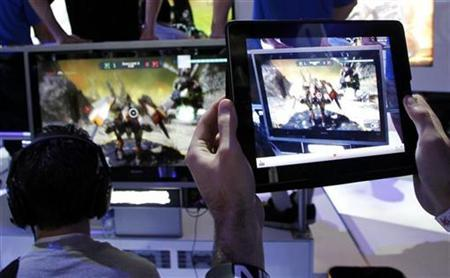 A man uses an Apple iPad to record a man playing ''Star Hawk'' on the PlayStation 3 (PS3) during the Electronic Entertainment Expo or E3 in Los Angeles June 7, 2011. REUTERS/Danny Moloshok