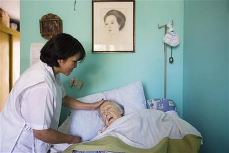 An elderly woman who is terminally ill receives attention in a room at the senile dementia building at the Canevaro old people's home in Lima March 25, 2010. REUTERS/Enrique Castro-Mendivil