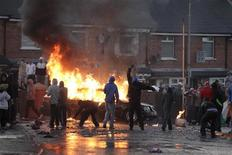 <p>Nationalist youths are seen near a burning car during a protest in the Ardoyne area of North Belfast July 12, 2011. REUTERS/Cathal McNaughton</p>