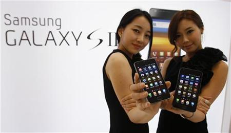 Models pose with Samsung Electronics' new smartphone Galaxy S II at the company's headquarters in Seoul April 28, 2011. REUTERS/Truth Leem