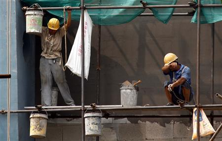 Workers stand atop scaffolding on a residential building construction site in central Beijing July 13, 2011. REUTERS/David Gray
