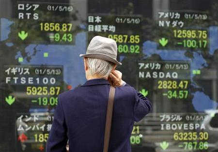 A man looks at an electronic board displaying various market indices from around the world outside a brokerage in Tokyo May 16, 2011. REUTERS/Toru Hanai