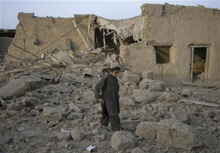 A boy walks past a mud house damaged by a bomb explosion early morning in the Pakistan-Afghanistan border town of Chaman July 14, 2011. REUTERS/Saeed Ali Achakzai
