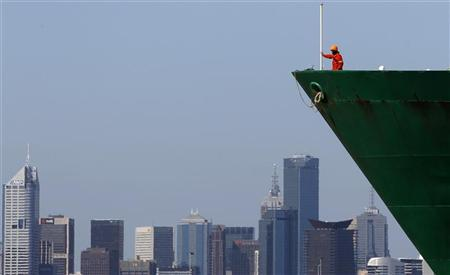 A man is seen on the bow of a container ship as it travels past the skyline of Melbourne October 19, 2010. REUTERS/Mick Tsikas
