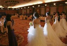 <p>Single women wear wedding dresses during a matching-making ball with Chinese male billionaires in Beijing December 20, 2009. REUTERS/Song Xiaonan/Handout</p>