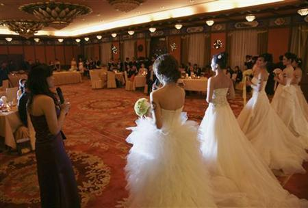 Single women wear wedding dresses during a matching-making ball with Chinese male billionaires in Beijing December 20, 2009. REUTERS/Song Xiaonan/Handout