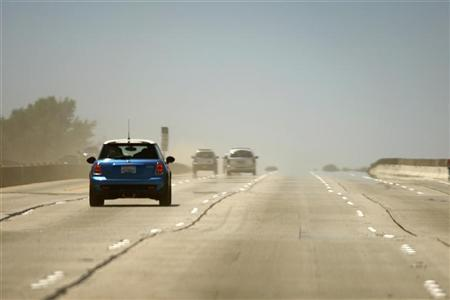 Cars pass through dust as the 405 freeway reopens ahead of schedule after the partial demolition of the Mulholland Drive bridge in Los Angeles, California July 17, 2011. REUTERS/David McNew