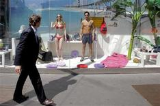 <p>A man walks past models posing as mannequins as part of a protest in a COIN department store window in downtown Milan July 18, 2011. REUTERS/Alessando Garofalo</p>