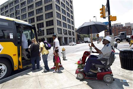 Tommy Fowler (R) shields himself from the sun as he waits to board a bus during a prolonged heat wave in Dallas, Texas July 18, 2011. REUTERS/Mike Stone