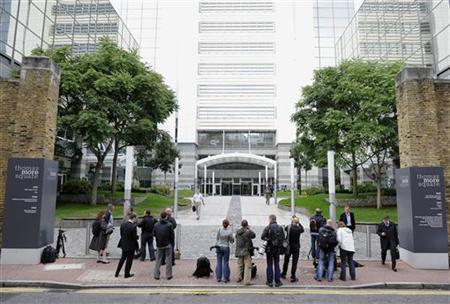 Journalists stand at the entrance to News International offices in Wapping, London, July 7, 2011. REUTERS/Paul Hackett