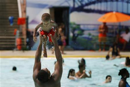 A man tosses a small child in the air while standing in the water at the Astoria Park Pool in New York July 21, 2011. REUTERS/Lucas Jackson