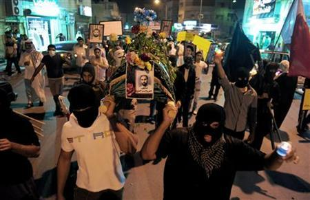 Protesters hold a mock coffin of Muhammad Hayak, who disappeared in 1996, and pictures of men said to be held prisoner without trial during a protest asking for the release of prisoners, and the withdrawal of Saudi troops from neighbouring Bahrain, in Saudi Arabia's eastern Gulf coast town of Qatif April 14, 2011. REUTERS/Stringer
