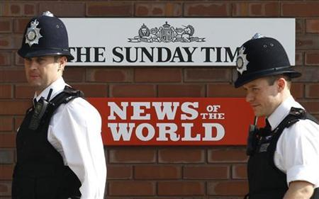 Police officers stand outside an entrance to News International in London July 10, 2011. REUTERS/Luke MacGregor