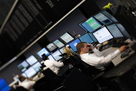 Traders are pictured at their desks at the Frankfurt stock exchange July 12, 2011. Picture taken with a tilt and shift lens. REUTERS/Alex Domanski