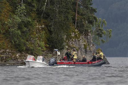 Rescue boats patrol near the shore of the small, wooded island of Utoeya July 23, 2011, after a suspected right-wing Christian gunman in police uniform killed at least 84 people in a ferocious attack on a youth summer camp of Norway's ruling Labour party, and hours after a bomb killed seven in Oslo. Witnesses said the gunman, identified by police as a 32-year-old Norwegian, moved across the island of Utoeya in a lake northwest of Oslo on Friday, firing at young people who scattered in panic or tried to swim to safety. REUTERS/Fabrizio Bensch