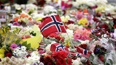 A Norwegian flag is placed amongst floral tributes outside the Oslo cathedral July 24, 2011. REUTERS/Cathal McNaughton