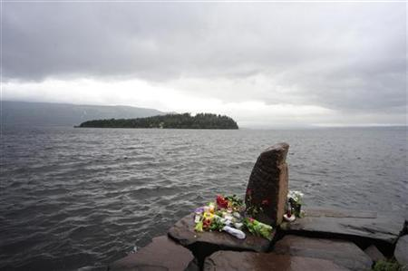 Flowers are placed at the Utvika campsite where victims were evacuated to from Utoeya Island (background) during Friday's shooting massacre, July 24, 2011. REUTERS/Sindre Thoresen Lonnes
