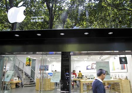 A pedestrian uses his cell phone as he walks past a fake Apple store in Kunming, Yunnan province July 21, 2011. A fake Apple store in China, made famous by a blog that said even the staff working there didn't realise it was a bogus outlet, is probably the most audacious example to date of the risks Western companies face in the booming Chinese market. The less-publicised phenomenon of unauthorised vendors setting up shop to peddle real products has grown alongside China's manufacturing prowess. Many of the factories that produce brand-name goods on contract have been known to do extra runs of the goods to make extra cash, analysts say. Picture taken July 21, 2011. REUTERS/China Daily