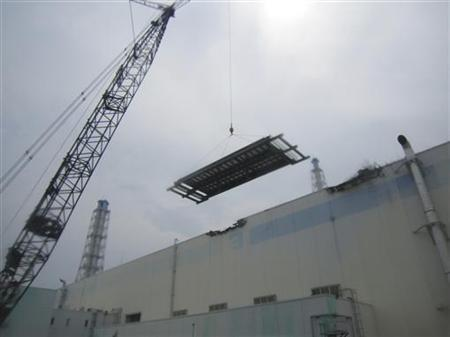 The installation work of a roof at unit 3 turbine building at the tsunami-crippled Fukushima Daiichi Nuclear Power Station in Fukushima prefecture is seen in this July 18, 2011 handout photo. REUTERS/Tokyo Electric Power Co/Handout