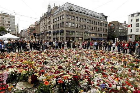 People pay their respects at a sea of floral tributes to the victims of Friday's attacks, outside the cathedral of Oslo July 25, 2011. REUTERS/Cathal McNaughton