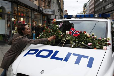 A woman places flowers on a police vehicle after a memorial march to mourn for the victims of the killing spree and bomb blast in Oslo July 25, 2011. REUTERS/Wolfgang Rattay