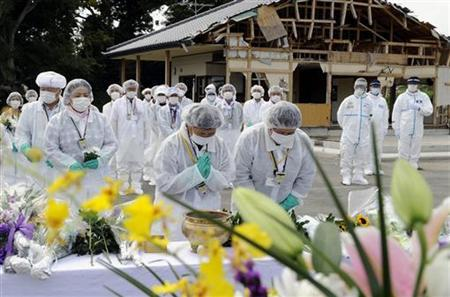 Evacuees from Okuma, in white protective suits, return to Okuma to offer prayers for the victims of March 11's earthquake and tsunami disaster, in Fukushima prefecture July 24, 2011. REUTERS/Kyodo FOR EDITORIAL USE ONLY. NOT FOR SALE FOR MARKETING OR ADVERTISING CAMPAIGNS. THIS IMAGE HAS BEEN SUPPLIED BY A THIRD PARTY. IT IS DISTRIBUTED, EXACTLY AS RECEIVED BY REUTERS, AS A SERVICE TO CLIENTS. JAPAN OUT. NO COMMERCIAL OR EDITORIAL SALES IN JAPAN