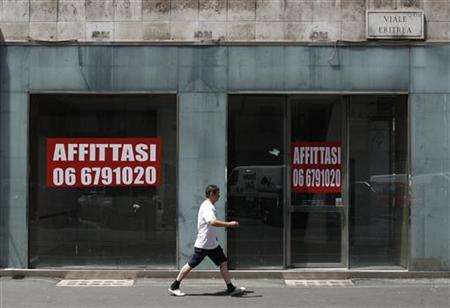 A man walks past a shop with signs reading, ''for rent'' in downtown Rome July 13, 2011. REUTERS/Tony Gentile