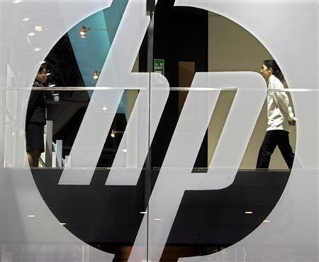 An employee walks past a Hewlett-Packard logo during the second day of the International Telecommunication Union (ITU) Telecom World 2006 in Hong Kong December 5, 2006. REUTERS/Paul Yeung