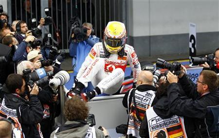 McLaren Formula One driver Lewis Hamilton of Britain jumps over a fence to reach his mechanics to celebrate after winning the German F1 Grand Prix at the Nuerburgring circuit July 24, 2011. REUTERS/Kai Pfaffenbach