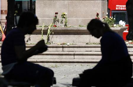 Flowers are placed at the base of a monument in respect of the victims in last Friday's killing spree and bomb attack in Oslo, July 27, 2011. REUTERS/Cathal McNaughton