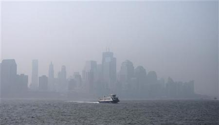 A thick haze hangs over the skyline of Lower Manhattan as a ferry crosses the Hudson River in New York, July 21, 2011. REUTERS/Gary Hershorn