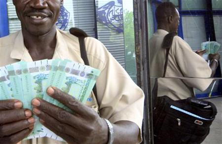 A person counts after receiving the new Sudanese currency from a cashier at a branch of the central bank of Sudan in Khartoum July 24, 2011. REUTERS/ Mohamed Nureldin Abdallah