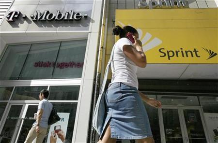 A woman talks on her phone as she walks past T-mobile and Sprint wireless stores in New York in this July 30, 2009 file photo.REUTERS/Brendan McDermid